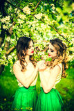 Dwa szczęśliwej ładnej dziewczyny zostaje pod okwitnięcie jabłonią Zdjęcia Stock