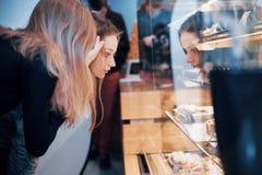 Dwa szczęśliwej atrakcyjnej dziewczyny wybiera ganaches, praline i czekolady wyśmienicie, Obraz Stock