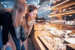 Dwa szczęśliwej atrakcyjnej dziewczyny wybiera ganaches, praline i czekolady wyśmienicie, Zdjęcie Stock