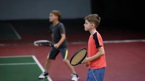 Dwa szczęśliwej chłopiec słuzyć piłki na sądzie z kantem i wraca Dzieci uderza forehanda w tenisowym mieć lekcję zbiory wideo