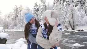 Dwa szczęśliwej dziewczyny śmia się ściskający each inny blisko rzeki w śnieżne lasowe kochanek dziewczyny cieszą się spacer zbiory wideo