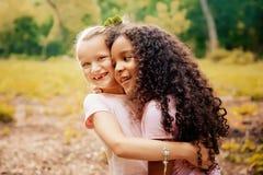 Dwa szczęśliwej dziewczyny jako przyjaciele ściskają each inny w rozochoconym sposobie Małe dziewczyny w parku Zdjęcie Royalty Free