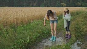 Dwa szczęśliwej dziewczyny siostry w butach bawić się w kałuży deszczówka na wiejskiej drodze zdjęcie wideo