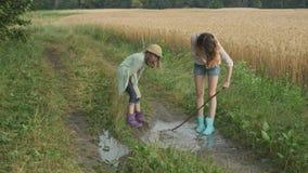Dwa szczęśliwej dziewczyny siostry w butach bawić się w kałuży deszczówka na wiejskiej drodze zbiory wideo