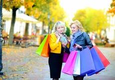 Dwa szczęśliwej dziewczyny w okularach przeciwsłonecznych z torbami na zakupy, używają uśmiech i smartphone obrazy stock