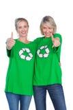 Dwa szczęśliwej kobiety jest ubranym zieleń przetwarza tshirts daje aprobatom Obraz Stock