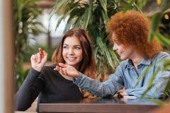 Dwa szczęśliwej kobiety opowiada w kawiarni i wskazuje daleko od zdjęcie stock