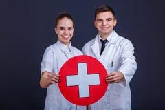 Dwa szczęśliwej lekarki facet, dziewczyna chwyta medycznego znak, bielu krzyż w czerwonym okręgu i uśmiech, Fotografia Royalty Free