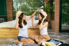 Dwa szczęśliwej młodej kobiety podczas gdy pakujący walizki dla wakacje lub wycieczki w domu fotografia royalty free