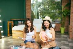 Dwa szczęśliwej młodej kobiety podczas gdy pakujący walizki dla wakacje lub wycieczki w domu zdjęcia royalty free