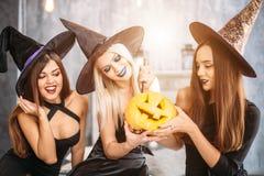 Dwa szczęśliwej młodej kobiety w czarnych czarownicy Halloween kostiumach na przyjęciu Zdjęcia Royalty Free