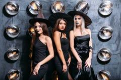 Dwa szczęśliwej młodej kobiety w czarnych czarownicy Halloween kostiumach na przyjęciu Zdjęcie Royalty Free