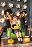 Dwa szczęśliwej młodej kobiety w czarnych czarownicy Halloween kostiumach na przyjęciu Fotografia Stock