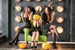 Dwa szczęśliwej młodej kobiety w czarnych czarownicy Halloween kostiumach na przyjęciu Obraz Stock