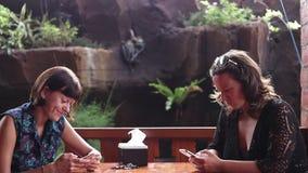 Dwa szczęśliwej młodej kobiety z smartphones w jawnej kawiarni, azjatykcia restauracja Tropikalna Bali wyspa, Indonezja giro zbiory