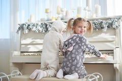 Dwa szczęśliwej małej dziewczynki w piżamach bawić się pianino na święto bożęgo narodzenia Zdjęcie Royalty Free