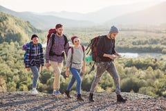 Dwa szczęśliwej pary chodzi w górach z mapą Młody caucasian mężczyzna wybiera właściwą wskazówkę z mapą Podróż zdjęcia royalty free