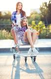 Dwa szczęśliwej pięknej nastoletniej dziewczyny jedzie wózek na zakupy outdoors Zdjęcie Royalty Free