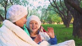 Dwa szczęśliwej uśmiechniętej dziewczyny siedzą w parka i falowania rękach kamera Dzieci w tle kwiecenie uprawiają ogródek zbiory wideo
