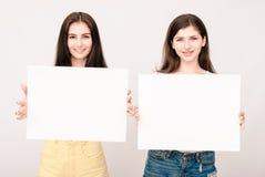 Dwa szczęśliwej uśmiechniętej młodej kobiety dba dużego pustego signboard obraz royalty free