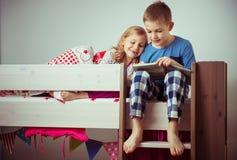 Dwa szczęśliwych rodzeństw dzieci czytelnicza książka w koi łóżku obrazy stock