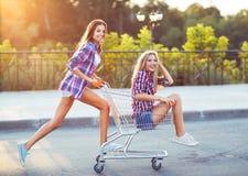 Dwa szczęśliwej pięknej nastoletniej dziewczyny jedzie wózek na zakupy outdoors Obrazy Stock