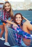 Dwa szczęśliwej pięknej nastoletniej dziewczyny jedzie wózek na zakupy outdoors Zdjęcia Royalty Free