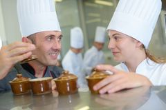 Dwa szefa kuchni uśmiecha się ramekin garnki i trzyma zdjęcia stock