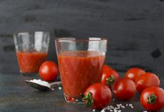 Dwa szkła świeży pomidoru sok z solą, czereśniowi pomidory na ciemnym tle obraz royalty free