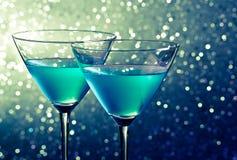 Dwa szkła błękitny koktajl na ciemnozielonym odcieniu zaświecają bokeh Zdjęcie Stock