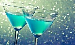 Dwa szkła błękitny koktajl na ciemnozielonym odcieniu zaświecają bokeh Obraz Stock