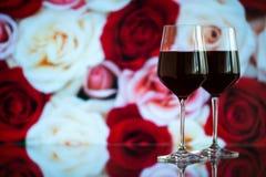Dwa szkła czerwone wino przeciw bokeh tłu z błyskają i róże Bardzo płytka głębia pole Zdjęcia Stock
