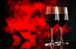 Dwa szkła czerwone wino przeciw bokeh tłu z błyskają i róże Bardzo płytka głębia pole Obraz Stock