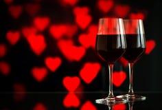 Dwa szkła czerwone wino przeciw bokeh tłu z błyskają i róże Bardzo płytka głębia pole Zdjęcie Royalty Free