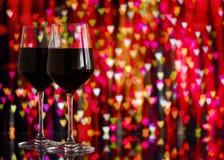 Dwa szkła czerwone wino przeciw bokeh tłu z błyskają i róże Bardzo płytka głębia pole Obrazy Stock