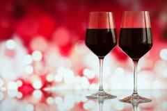 Dwa szkła czerwone wino przeciw bokeh tłu z błyskają i róże Bardzo płytka głębia pole Fotografia Stock