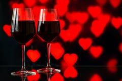 Dwa szkła czerwone wino przeciw bokeh tłu z błyskają i róże Bardzo płytka głębia pole Zdjęcia Royalty Free