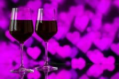 Dwa szkła czerwone wino przeciw bokeh tłu z błyskają i róże Bardzo płytka głębia pole Zdjęcie Stock