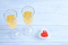 Dwa szkła iskrzasty szampan i czerwona sercowata świeczka obrazy royalty free
