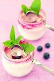 Dwa szkła jogurtu deser na różowym tle z spo, Obraz Stock
