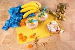 Dwa szkła koktajl, orzechy włoscy, pęcherzyca, wysuszone morele, banany, liście mennica na kolorowym tle Zdjęcie Stock