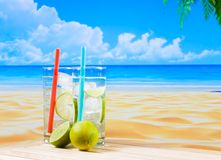 Dwa szkła koktajl z wapno plasterkiem na plamy palmie i plaży Zdjęcia Stock