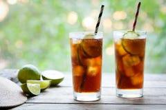Dwa szkła Kuba Libre koktajlu z kolą, lodem, wapnem i rumem na drewnianym stole z widokiem tarasu, z bliska Obraz Royalty Free