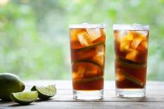 Dwa szkła Kuba Libre koktajlu z wapnem, lodem, mennicą, rumem na drewnianym stole z słomianym kapeluszem i widokiem taras, Zdjęcie Stock