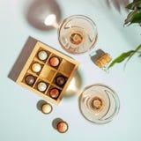 Dwa szkła szampan lub wino w szkła pudełku czekolady robić czekoladowy pastelowy błękitny tło biały i ciemny zdjęcie stock