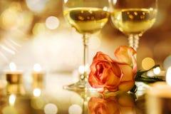 Dwa szkła z białym winem i różą kwitną na bokeh tle Zdjęcia Stock
