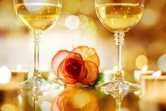 Dwa szkła z białym winem i różą kwitną na bokeh tle Obrazy Stock