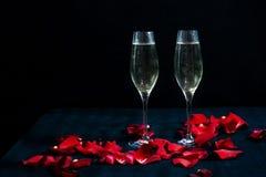 Dwa szkła z białymi płatkami czerwone róże na czarnym tle i szampanem obraz royalty free