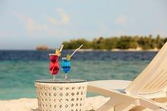 Dwa szkła z koktajlami na stołowym pobliskim plażowym krześle z błękitnym oceanem i białym piaskiem na tle ławki lub pokładu Zdjęcie Royalty Free