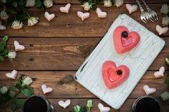 Dwa torta w postaci serc na drewnianym stole Obrazy Stock
